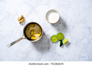 Overhead of sliced ginger in simple syrup with white sugar and sliced limes on white marble surface.