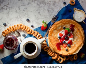 Overhead stack of thin pancakes poured with sour cream and decorated with fresh strawberries and blueberries. The concept of Russian tea party at holiday Maslenitsa, Shrovetide.