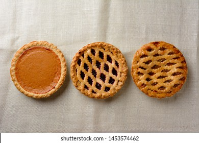 Overhead still life of fresh baked holiday pies on a burlap table cloth.