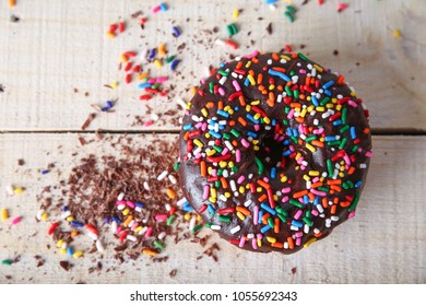 overhead studio shot of a donut with sprinkles on a wooden background unhealthy food concept