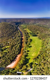 Overhead top down view over river stream of Colo River around Colo Heights area of the Gread Dividing range in Australia in vertical panorama under blue sky.