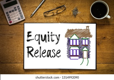 Overhead top view of Equity Release written in book on desk with a coloured house.  Desk has coffee cup, glasses, pen and calculator.