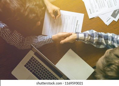 overhead top view of two workers in casual in the office signing the contract agreement on the table