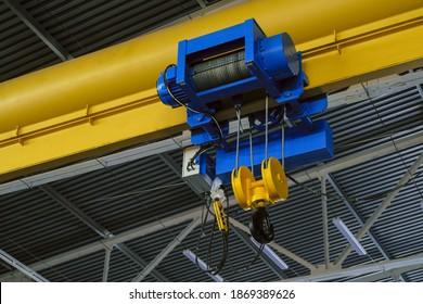 Overhead traveling cathead with steel hooks in industrial engeenering plant shop. Steel slings.
