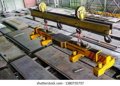 Overhead traveling crane with magnetic grippers traverse for lifting steel sheets. Industrial indoors area.