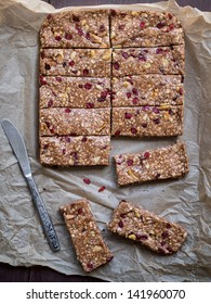 Overhead vertical photo of cut into servings homemade organic granola (muesli) protein power bars with peanut butter, honey, nuts and dry berberis on a piece of baking paper. Knife on the side.