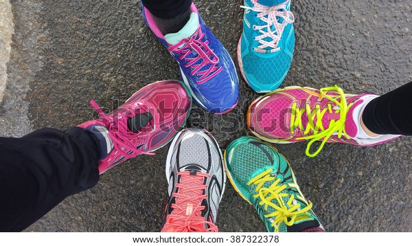 Overhead view of 6 brighlty colored runners' shoes on wet pavement