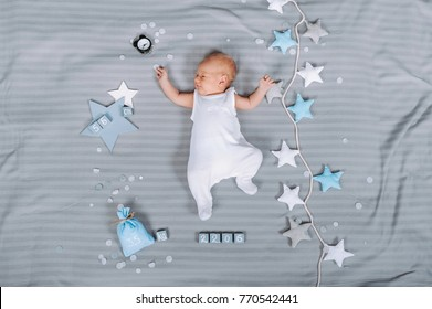overhead view of adorable newborn baby in bodysuit lying on bed with decorations around