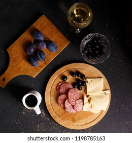Overhead view of aperitif table Meat snack, fried sausages, cheese, salami, olives and a glass of wine on a dark table Menu and restaurant concept