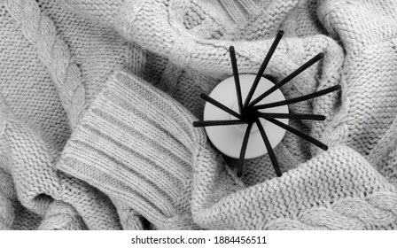 Overhead view at aroma reed diffuser on gray woolen knitwear. Ultimate gray color of the year 2021