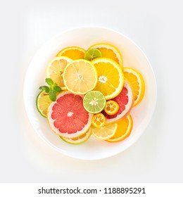 Overhead view of assorted citrus fruits slice on white background.