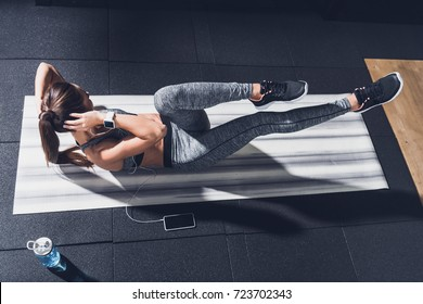 overhead view of athletic woman listening music in earphones while doing abs exercises on mat