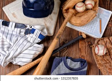 Overhead view of baseball gear on a rustic wood surface. Items include, Home Plate, helmet, baseball, ball, glove, catchers mitt, score book, pants, belt and bats.