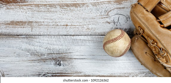 Overhead view of baseball and mitt on white vintage wood
