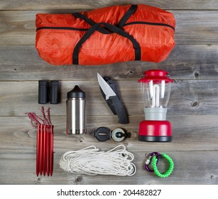 Overhead view of basic hiking gear placed on weathered wooden boards. Items include tent inside of bag, pegs, compass, canteen, rope, knife, case, lantern and binoculars.