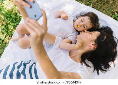 Overhead view of beautiful pretty mother and her little fun smiling daughter playing outdoor and making selfie on smartphone. Cute mom and child play in the park. Happy family make selfie. Motherhood.