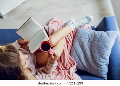 Overhead view of   beautiful  young woman   sitting on couch  with sketchpad  drinking tea and looking into the window.