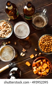 Overhead view of beer glasses, beer dottkes and snacks on wooden table. Focus on beer