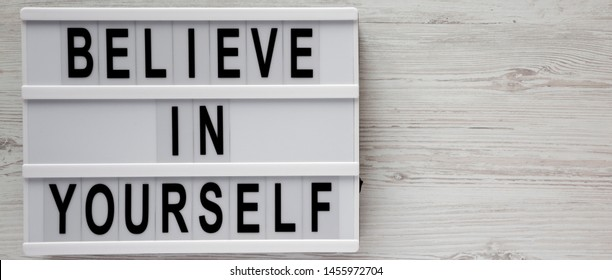 Overhead view, 'Believe in yourself' words on a lightbox on a white wooden background, top view. From above, flat lay, overhead. Space for text.