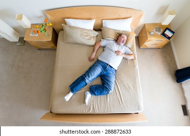 Overhead view of a big overweight middle-aged man with a goatee lying sprawled diagonally in his socks on a king size bed taking a midday nap over the weekend