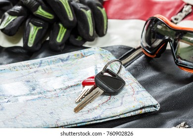 Overhead view of biker accessories. Items included motorcycle goggles, gloves, keys and jacket. Motorcycle travel dream concept.