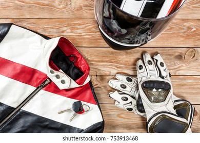 Overhead view of biker accessories placed on rustic wooden table. Items included motorcycle helmet, gloves, keys and jacket. Motorcycle travel dream concept.