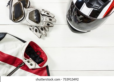 Overhead view of biker accessories placed on white wooden table. Items included motorcycle helmet, gloves and jacket. Motorcycle travel dream concept.