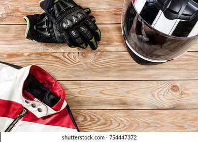 Overhead view of biker accessories placed on rustic wooden table. Items included motorcycle helmet, gloves and jacket. Motorcycle travel dream concept.