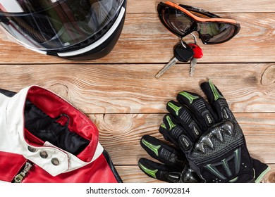 Overhead view of biker accessories placed on rustic wooden table. Items included motorcycle helmet, gloves, keys, goggles and jacket. Motorcycle travel dream concept.