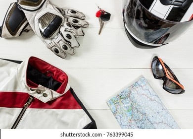 Overhead view of biker accessories placed on white wooden table. Items included motorcycle helmet, gloves, keys, map, goggles and jacket. Motorcycle travel dream concept.