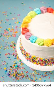 overhead view of a Birthday cake with rainbow icing and colorful Sprinkles over a blue background.