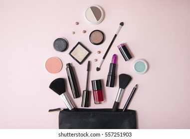 Overhead view of a black leather make up bag, with cosmetic beauty products spilling out on to a pastel pink background