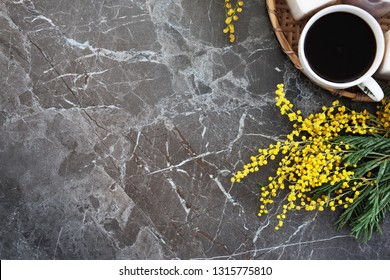 Overhead view of a bouquet of yellow mimosa pattern on a black marble table. Flat lay, top view - Image