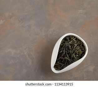 Overhead view of bowl with dry tea on the table. Copyspace