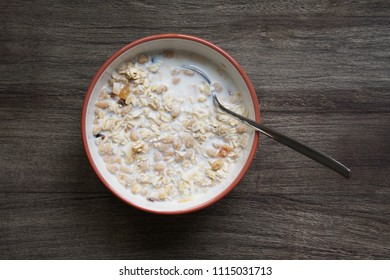 overhead view of bowl of muesli with milk on wooden table