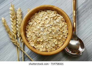 Overhead view of a bowl of Oats with copy space on a wooden grey background
