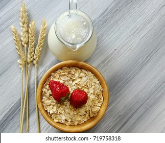 Overhead view of a bowl of Oats milk and strawberries with copy space on a wooden grey background