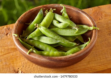Overhead view of bowl with pea pods on wooden background. Health eating concept. Homegrown food