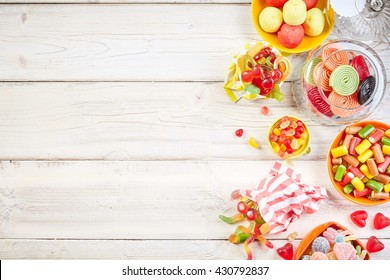 Overhead view of bowls filled with candy and other yummy confections beside glass jar with rolled licorice