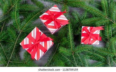 Overhead view of boxed gifts with Christmas tree branches on weathered wood