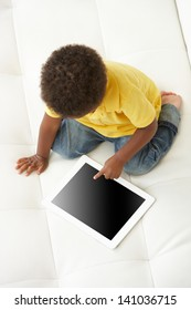 Overhead View Of Boy On Sofa Playing With Digital Tablet