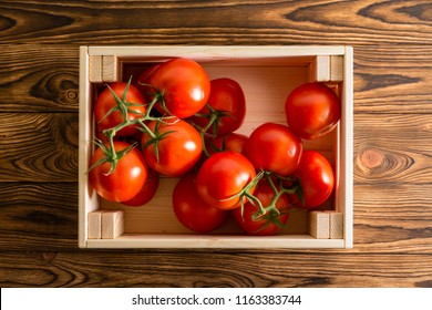Overhead view of bright red tomatoes in light colored wooden crate on top of wooden table background