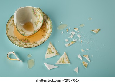 Overhead view of a Broken Elegant Vintage China Teacup with saucer dish, spilled tea and fractured shards of sharp glass fragments scattered on teal colored kitchen table background.  Horizontal
