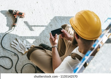 overhead view of builder in protective helmet using smartphone with blank screen at construction site