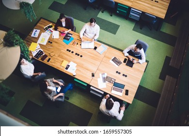 Overhead view of business people in formal wear gathering at conference desk with documents and laptop discussing work strategy in corporation