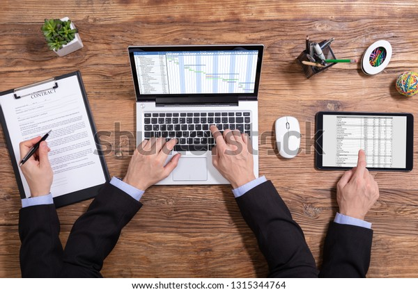 Overhead View Of A Businessman Doing Multitasking Work On Electronic Devices