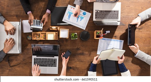 Overhead View Of Businesspeople Hands On Office Desk Using Electronic Devices