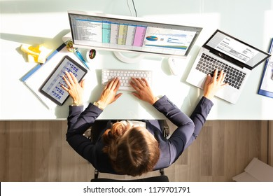 Overhead View Of A Businesswoman Doing Multitasking Work On Electronic Devices