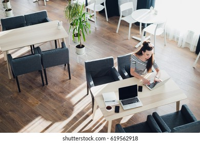 Overhead view of businesswoman at table of staff canteen, typing on a laptop.