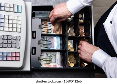 An Overhead View Of Cashier's Hand Taking Banknote From Opened Till